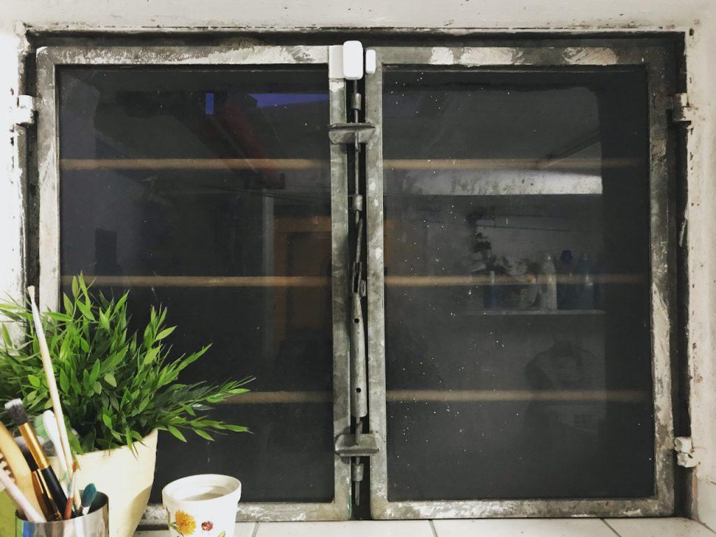 Xiaomi Aqara ZigBee Fenstersensor montiert auf einem Fenster mit Metallrahmen.