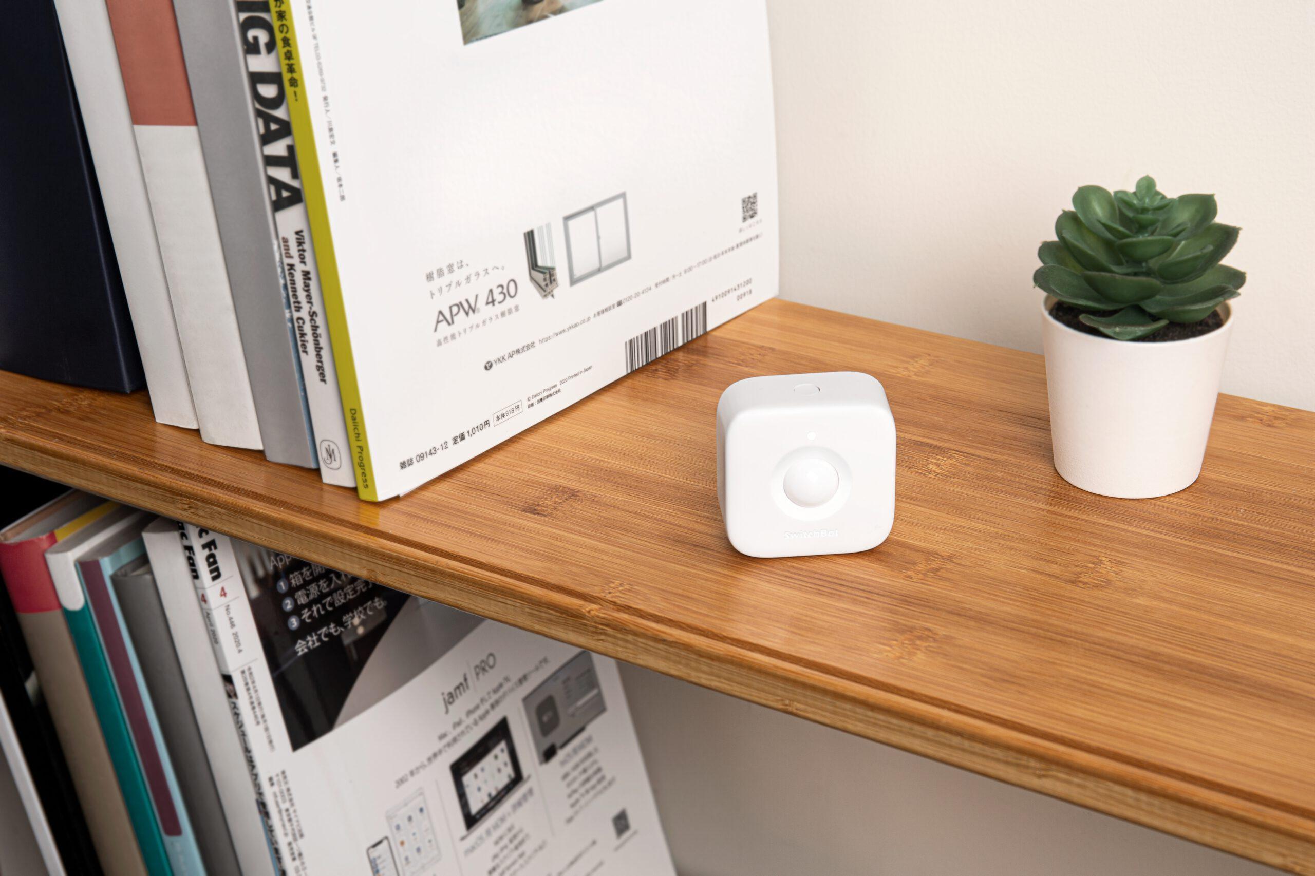 SwitchBot Bewegungsmelder der ohne Fuß aufgestellt oder mit Fuß ebenso and die Wand montiert werden kann.